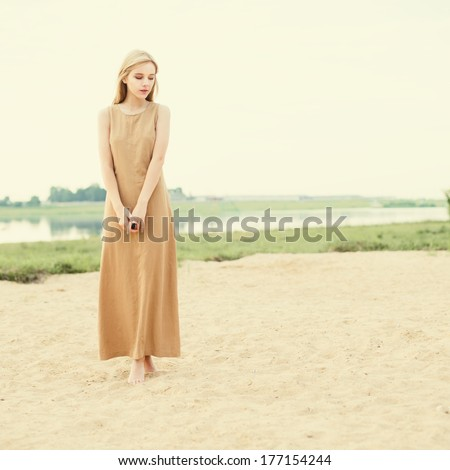 beautiful young blond woman in dress near the water - stock photo