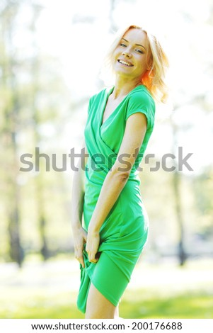 Beautiful young blond woman in green dress posing n spring park - stock photo