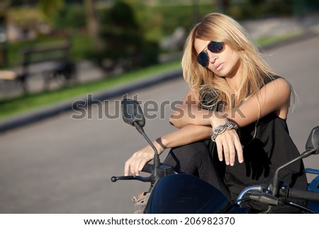 Beautiful young blond woman in sunglasses sitting on motorcycle  - stock photo