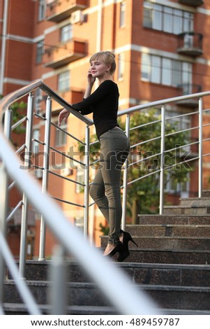 beautiful young blond woman in sunglasses standing on the stairs in the city. against the backdrop of the river and the city