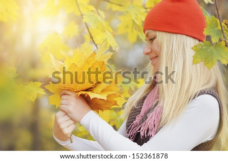 Beautiful young blond woman looking at a bouquet of yellow leaves of autumn