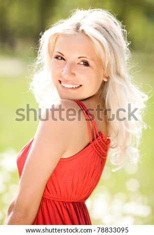 beautiful young blond woman  on the  meadow with white flowers  on a warm summer day - stock photo
