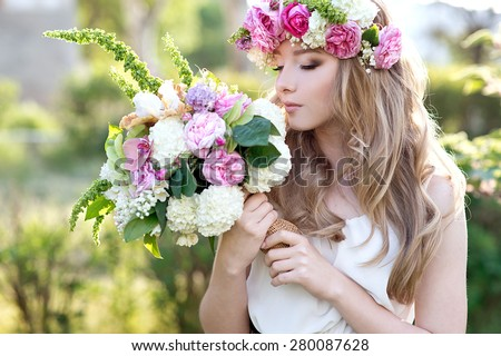 Beautiful young blond woman on the park with flower wreath and bouquet on a warm summer day. Bride. - stock photo