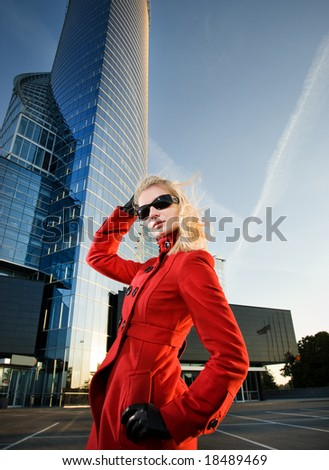 Beautiful young blond woman outdoors. Modern building behind her