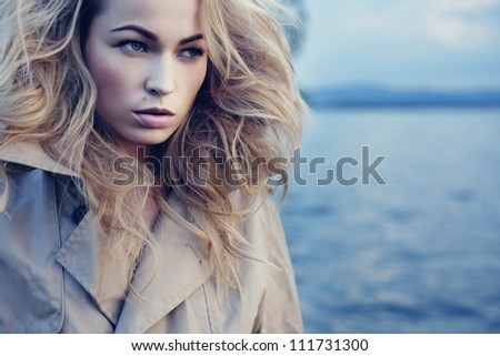 Beautiful young blond woman outdoors portrait near the lake - stock photo