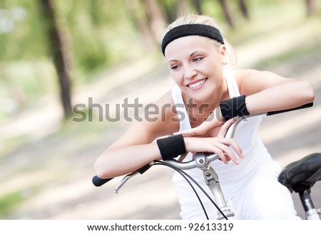 beautiful young blond woman  riding a bicycle on a warm summer day - stock photo