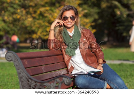 Beautiful young blond woman sitting on a bench in a park reading a book - stock photo