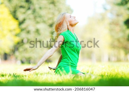 Beautiful young blond woman sitting on grass in park