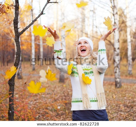 beautiful young blond woman spending time in the park and catching maple leaves - stock photo