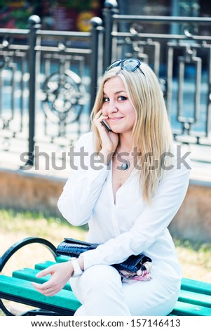 Beautiful young blond woman talk by phone outdoor