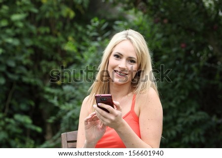 Beautiful young blond woman text messaging on her mobile phone while sitting on a wooden chair in the garden looking up to smile at the camera - stock photo