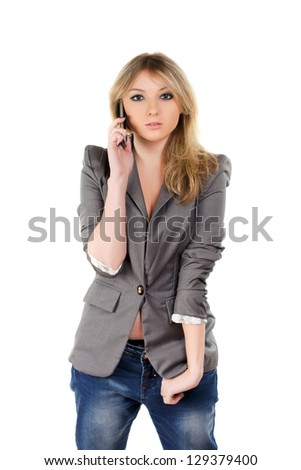 Beautiful young blond woman wearing grey jacket and speaking on the mobile phone. Isolated - stock photo