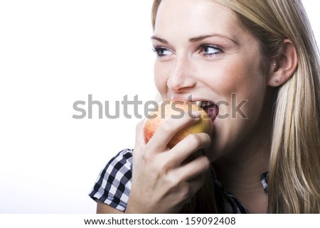 Beautiful young blond woman with an amused look and vivacious smile biting a fresh apple depicting a healthy diet and lifestyle