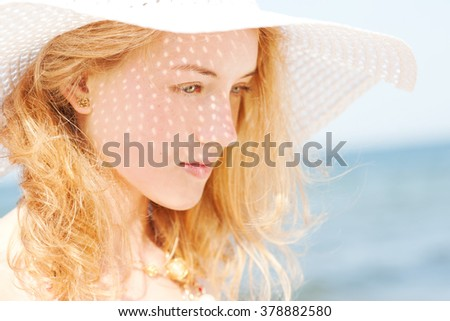 Beautiful young blond woman with beach hat - summer portrait - stock photo