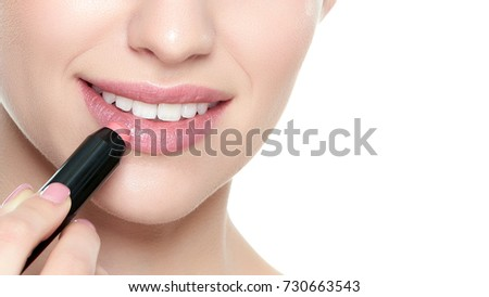 Beautiful young blond woman with sexy full lips applying coral color lipstick. Beauty portrait isolated over white background with copy space.