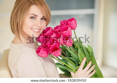 Beautiful young blond woman with tulip bouquet. Spring portrait. Bright pink flowers in girl's hands. At home. Interior portrait/ - stock photo