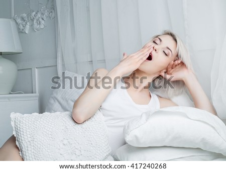 beautiful young blond woman yawning in bed at home