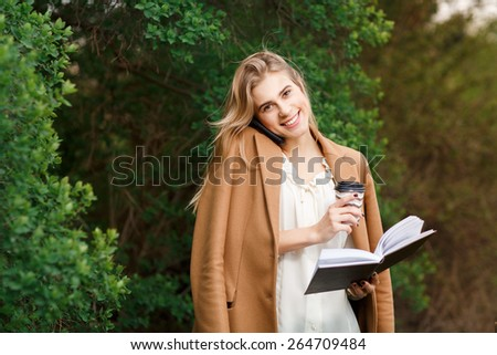 Beautiful young blonde Caucasian woman drinking takeaway coffee in park - stock photo