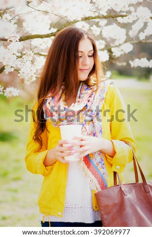 Beautiful young blonde Caucasian woman drinking takeaway coffee in park in spring. Pretty girl with sweater outdoors in fall with coffee cup smiling.