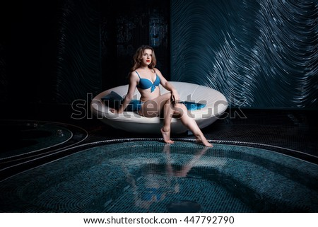 Beautiful young blonde caucasian woman in bikini relaxing in hot pool or jacuzzi at spa center, water treatment and body care concept - stock photo
