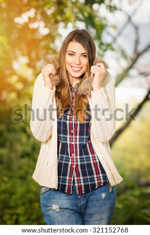 Beautiful young blonde Caucasian woman smiling wearing fashionable autumn outfit. Cute teenage girl in plaid shirt, denim jeans and beige sweater in fall in park. Vertical, retouched, vibrant colors. - stock photo