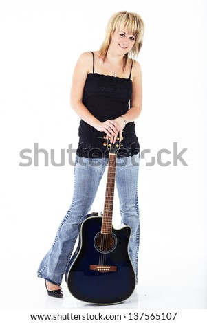 Beautiful young blonde caucasian woman standing with a blue acoustic guitar against a white background