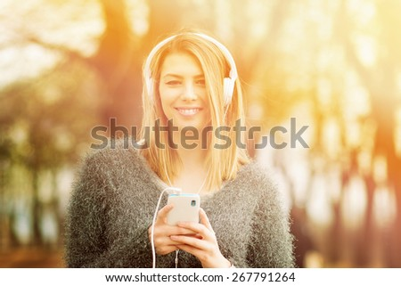 Beautiful young blonde Caucasian woman with smart phone and headphones listening to music outdoors on sunny spring day. Closeup, blurred background, retouched, horizontal. - stock photo