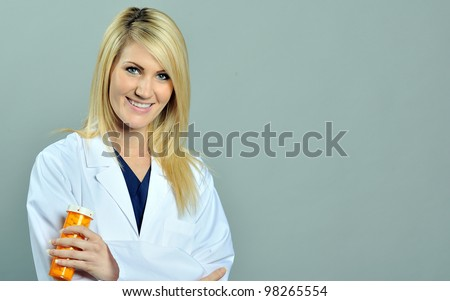 Beautiful young blonde female nurse or physician in blue scrubs and white lab coat holding a bottle of pills - stock photo