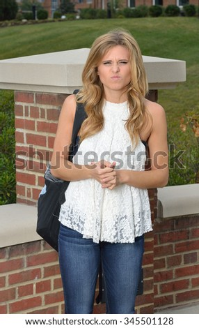 Beautiful young blonde female student on campus - crinkling face - stock photo