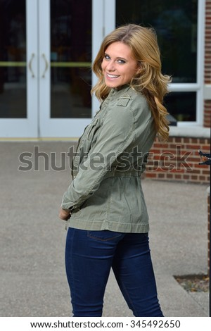 Beautiful young blonde female student on campus - fashion, green jacket and jeans - stock photo