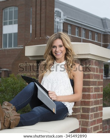 Beautiful young blonde female student on campus - sitting with a tablet computer - stock photo