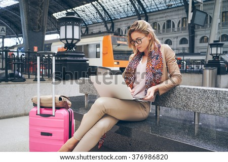 Beautiful young blonde female student using portable laptop computer. modern businesswoman using a laptop computer while waiting for the train - stock photo
