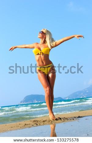 Beautiful young blonde fit woman in bikini on the beach - stock photo