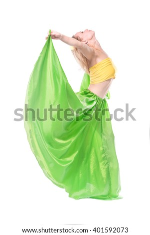 Beautiful young blonde girl in a yellow top, a long green skirt and a hairpin with a flower on her head dancing