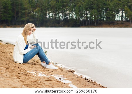 beautiful young blonde girl in jeans and a white shirt sitting on the shore of the frozen cold of the lake near the forest in early spring