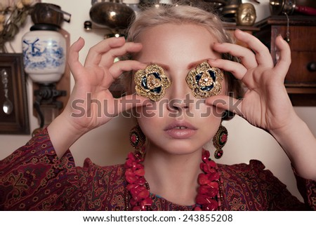 beautiful young blonde girl in retro interior in motley Turkish dress, brooches, earrings and a large red the necklace - stock photo