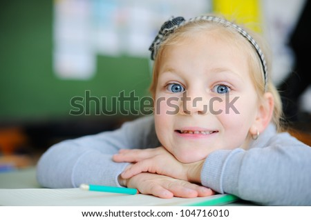 Beautiful young blonde girl in school - stock photo
