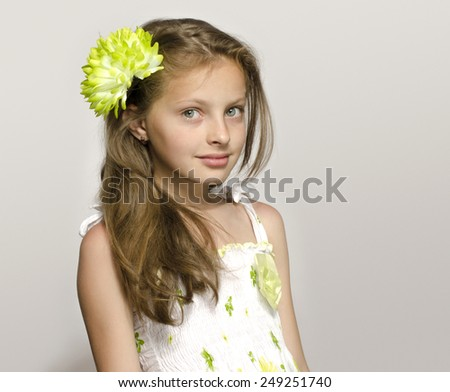 Beautiful young blonde girl in white dress smiling, portrait of an adorable kid. Little girl with a green big flower in her hair, smelling a flower - stock photo