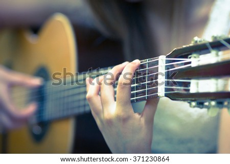 Beautiful young blonde girl with white dress playing a guitar in a sunset scenario - stock photo