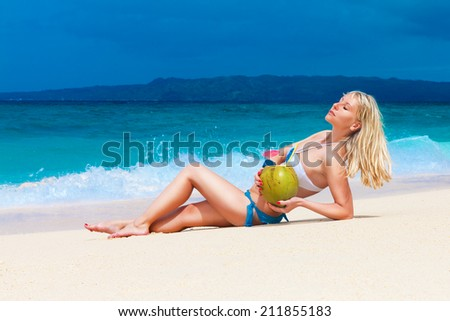 beautiful young blonde in bikini is lying on a tropical beach with coconut