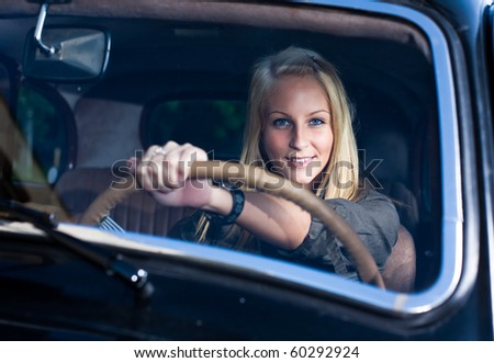 Beautiful young blonde posing with black vintage car. - stock photo