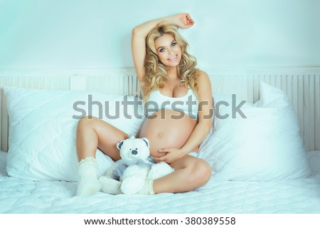 Beautiful young blonde pregnant woman lying in bed, looking at camera. Smiling happy girl. - stock photo
