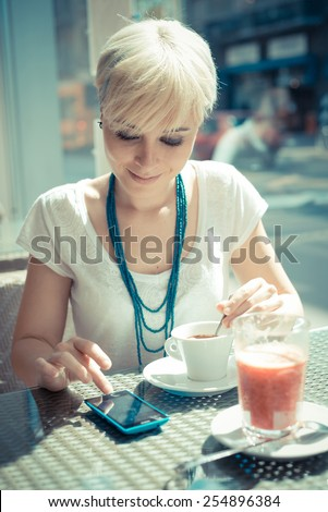 beautiful young blonde short hair hipster woman using smart phone at the cafe - stock photo