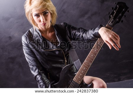 Beautiful young blonde siting on the amp dressed in black leather jacket with electric guitar on a black background - stock photo