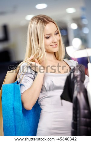 Beautiful young blonde smiles during clothes choice in shop - stock photo