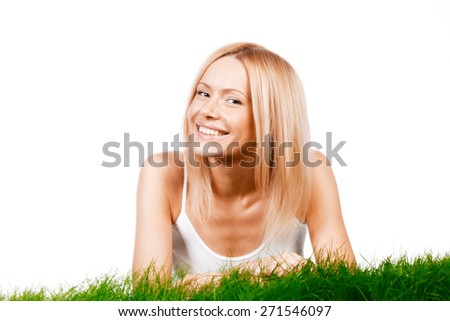 Beautiful young blonde smiling woman lying on grass, isolated on white background