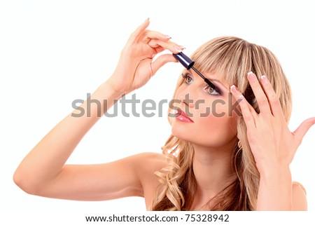 Beautiful young blonde woman applying mascara on her eyelashes - stock photo