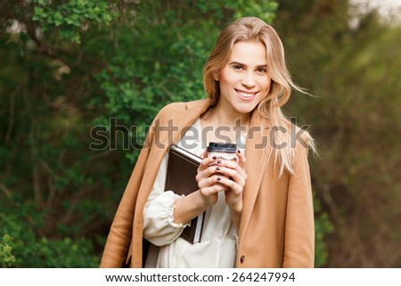Beautiful young blonde  woman drinking takeaway coffee in park  - stock photo
