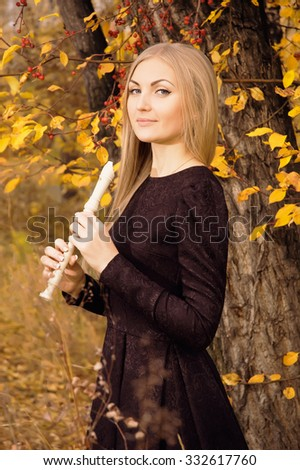 Beautiful young blonde woman elegant posing with flute recorder in autumn forest at sunset, ready to play music - stock photo
