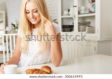 Beautiful young blonde woman enjoying a fresh crispy croissant and a mug of coffee for her breakfast